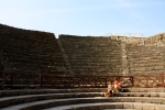 Two girls sitting in sunshine at the Pompeii Coliseum